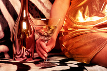 Beautiful Woman Drinks A Cocktail On A Rich Background. Female Hand With A Martini On The Background Of A Shiny Bottle And A Zebra Skin.