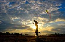 Silhouette Girl Holding Kite While Running On Land Against Sky During Sunset