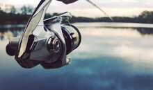 Fishing Rod And Spinning Reel Closeup With A Lake In The Background The Concept Of Rural Getaway. Article About Fishing Day.