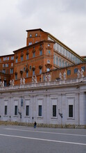 View Of The Apostolic Palace Or Palazzo Apostolico Or Papal Palace Or Palace Of The Vatican With The Bernini's Colonnade At The Piazza San Pietro Or St. Peter's Square.