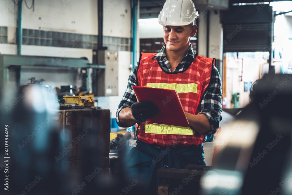 Fototapeta Manufacturing worker working with clipboard to do job procedure checklist . Factory production line occupation quality control concept .