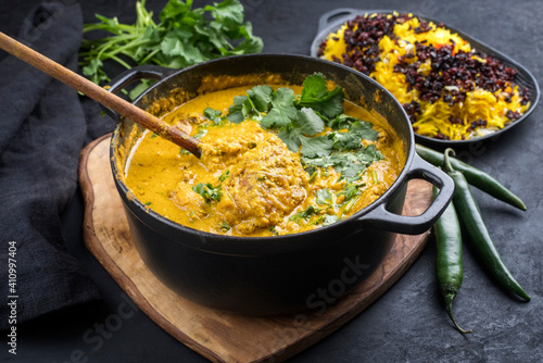 Traditional Indian chicken curry masala with saffron rice and berberis served as close-up in saucepan