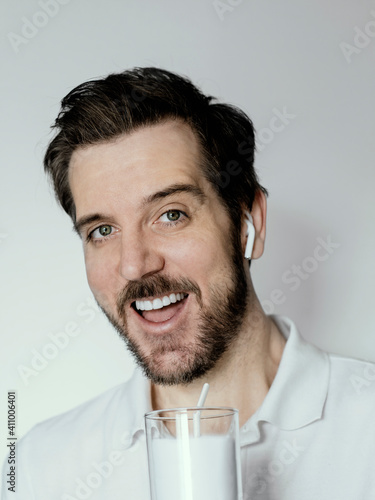 Man With A Big Smile Drinking White Milk While Wearing White Polo Shirt And White Earbud Headphones. © richard theis/EyeEm