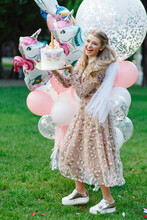 Portrait Of A Laughing Girl With A Cake In The Park. She's Wearing A Pink Dress And Carrying A Bunch Of Giant Balloons.