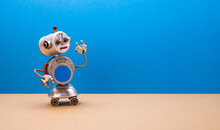 Metallic Chat Bot Robot On Blue Beige Background. Silver Color Domestic Robotic Roller With Empty Blue Interface On Body. Creative Design Steampunk Toy, Copy Space