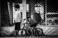 Children Playing With A Bicycle, Black And White