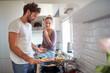 Leinwandbild Motiv A young couple in love enjoying preparing breakfast together in the kitchen. Cooking, together, kitchen, relationship