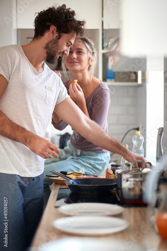 Fotografie, Obraz A young guy enjoying preparing a meal for his girlfriend