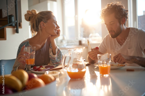 Obraz A happy young couple enjoying a beautiful sunny morning while having a breakfast together. Relationship, love, together, breakfast - fototapety do salonu