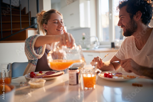 Obraz A happy young couple enjoying fresh orange juice for a breakfast. Relationship, love, together, breakfast - fototapety do salonu