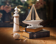 Wooden Sailboat Model On Books, Lighthouse And White Seashells, Vintage Style