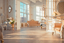 Rich Apartment Interior With Golden Baroque Decorations On The Walls And Luxury Furniture. The Room Is Flooded With The Rays Of The Setting Sun