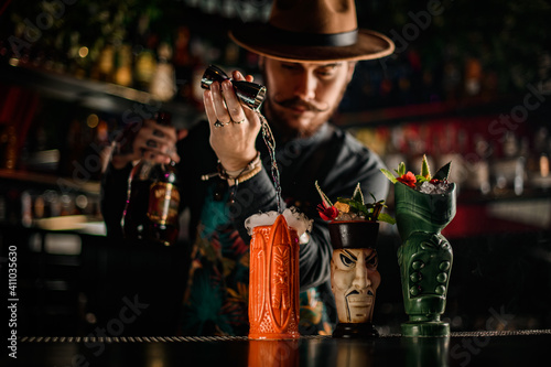 stylish bartender skillfully pours liquid into one of the fancy glasses on bar © fesenko