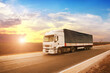 canvas print picture - A big truck with a trailer on a road against a sky with a sunset