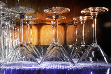 A Row Of Empty Champagne Glasses Stand On A Shelf, Upside Down.