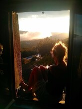 Side View Of Thoughtful Woman Looking Through Window At Sunset
