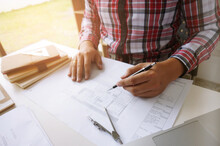 Midsection Of Architect With Pen Analyzing Blueprint On Office Desk