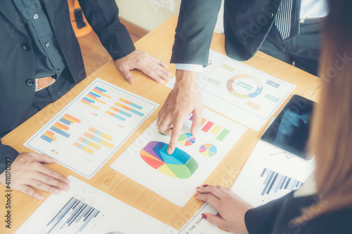 Business Colleagues With Colorful Graphs At Desk In Office
