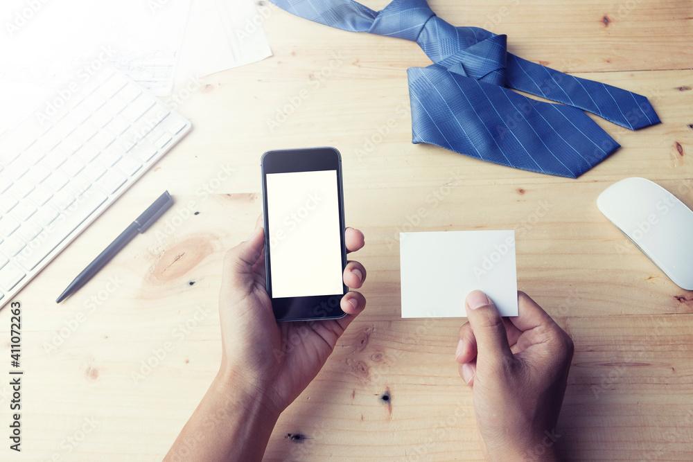 Fototapeta Cropped Hands Of Businessman Using Blank Phone At Desk