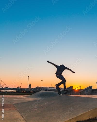 Fototapeta Rear View Of Man Skateboarding On Street Against Clear Sky During Sunset obraz