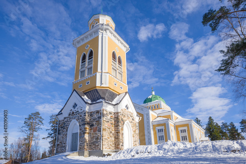 Foto Bell tower and largest wooden Lutheran church on a sunny March day