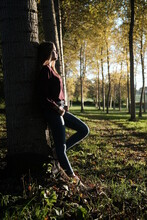 Girl Leaning On Tree In Forest