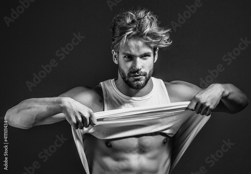 Handsome muscular sexy man in white vest has bare muscular torso and chest on grey background Wallpaper Mural