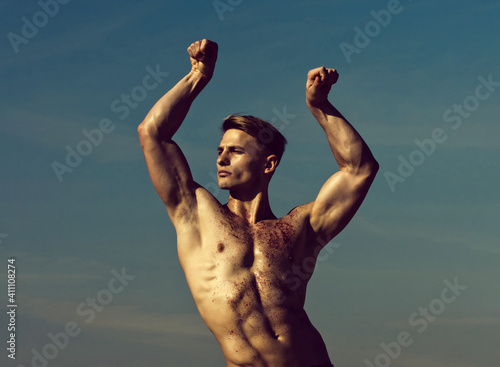 Obraz Man with glitter on bare chest. Athletic bodybuilder pose as hercules. Gladiator or atlant. Man with muscular wet body. - fototapety do salonu