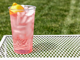 Fresh Squeezed Pink Lemonade In A Clear Cup With A Green Grassy Background With Copy Space.