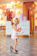 Cute Little Fashionista In Pajamas With A Pink Teddy Bear Toy. A Happy Baby Girl Tries On Outfits And Her Mother's Shoes In The Dressing Room.