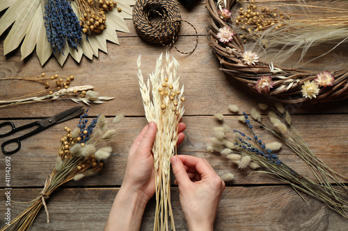 Fototapeta Florist making bouquet of dried flowers at wooden table, top view