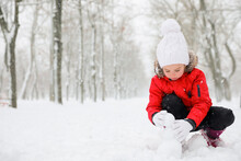 Cute Little Girl Making Snowballs Outdoors On Winter Day, Space For Text
