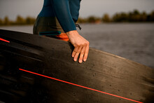 Close-up Of Man's Hand Holding Black Wakeboarding Board.