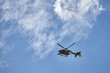 A Police Helicopter Flying In The Cloudy Blue Sky Over Madrid