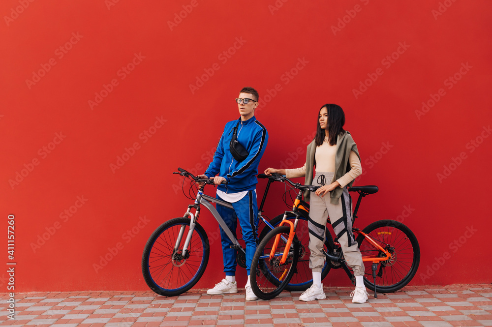 Fototapeta Stylish man and woman with bicycles stand on the street against the background of a red wall and look to the side, wearing sportswear.