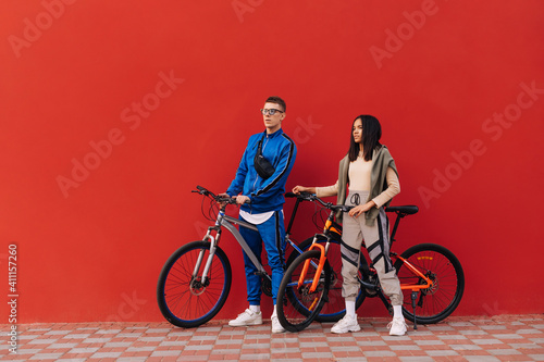 Obraz Stylish man and woman with bicycles stand on the street against the background of a red wall and look to the side, wearing sportswear. - fototapety do salonu