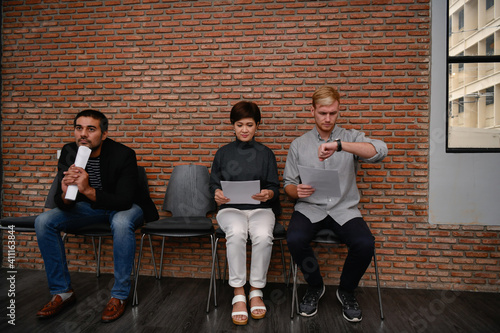 Obraz Full Length Of Business Colleagues Waiting While Sitting Against Brick Wall In Office - fototapety do salonu