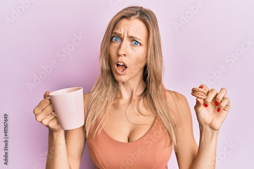 Obraz Beautiful caucasian woman drinking coffee and eating french pastry macaron in shock face, looking skeptical and sarcastic, surprised with open mouth - fototapety do salonu