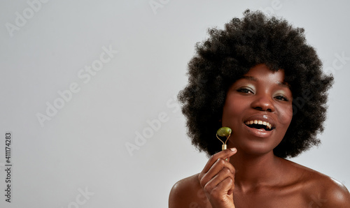Obraz Portrait of excited young african american woman with perfect glowing skin smiling at camera while massaging her face with jade roller, posing isolated over gray background - fototapety do salonu