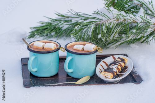 Two hot cocoa drink on a bed of snow and white background, close up © OlegD
