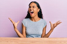 Young African American Girl Wearing Casual Clothes Sitting On The Table Crazy And Mad Shouting And Yelling With Aggressive Expression And Arms Raised. Frustration Concept.