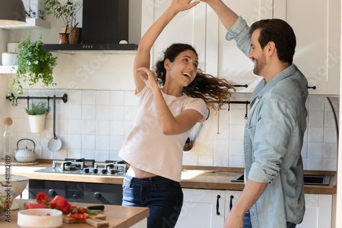 Obraz na plátně Romantic young spouses arrange disco party for two on quarantine at kitchen
