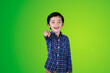 Leinwandbild Motiv Portrait Of Smiling Boy Standing Against Green Background
