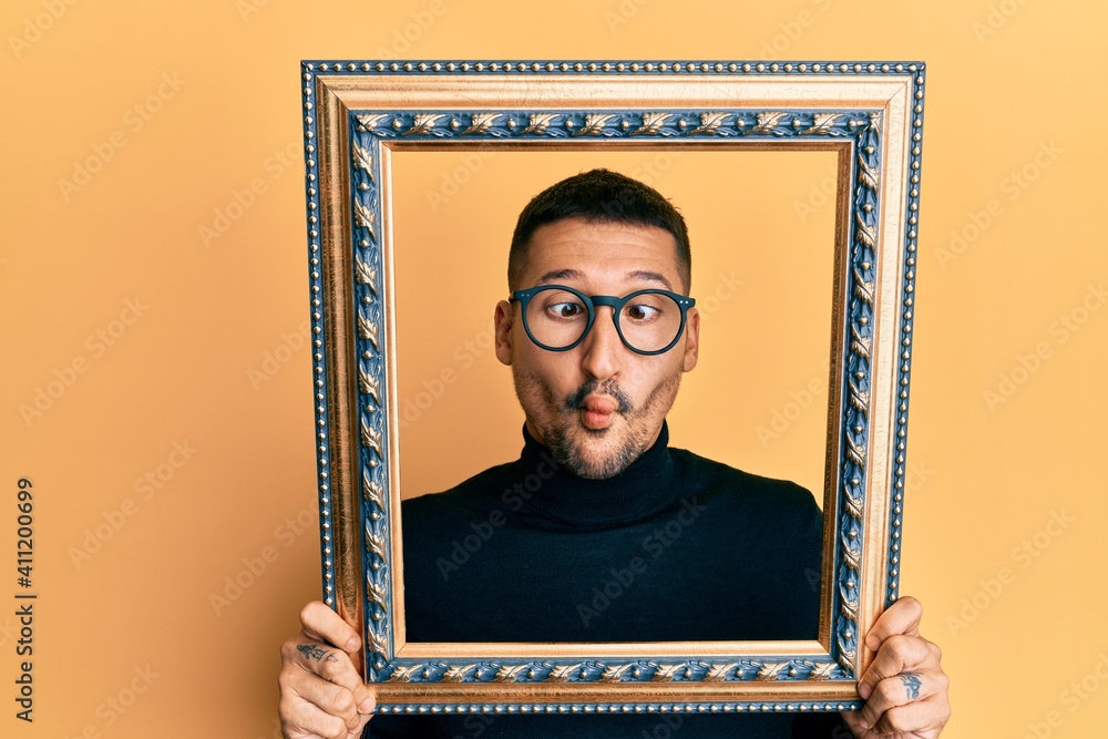 Fototapeta Handsome man with tattoos holding empty frame making fish face with mouth and squinting eyes, crazy and comical.