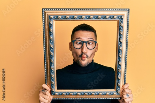 Photo Handsome man with tattoos holding empty frame making fish face with mouth and squinting eyes, crazy and comical