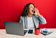 Beautiful Middle Age Woman Working At The Office Drinking A Cup Of Coffee Shouting And Screaming Loud To Side With Hand On Mouth. Communication Concept.