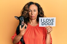 Middle Age Hispanic Woman Holding Chihuahua Dog And Paper With I Love Dogs Phrase Skeptic And Nervous, Frowning Upset Because Of Problem. Negative Person.