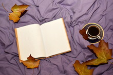 A Cup Of Coffee, Two Gingerbread Hearts, Dry Maple Leaves And A Blank Open Notebook On The Bed. Selective Focus, Copy Space