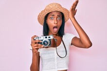 Young African American Woman Wearing Summer Hat Holding Vintage Camera Surprised With Hand On Head For Mistake, Remember Error. Forgot, Bad Memory Concept.