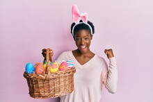 Young African American Girl Wearing Cute Easter Bunny Ears Holding Basket With Painted Eggs Screaming Proud, Celebrating Victory And Success Very Excited With Raised Arms